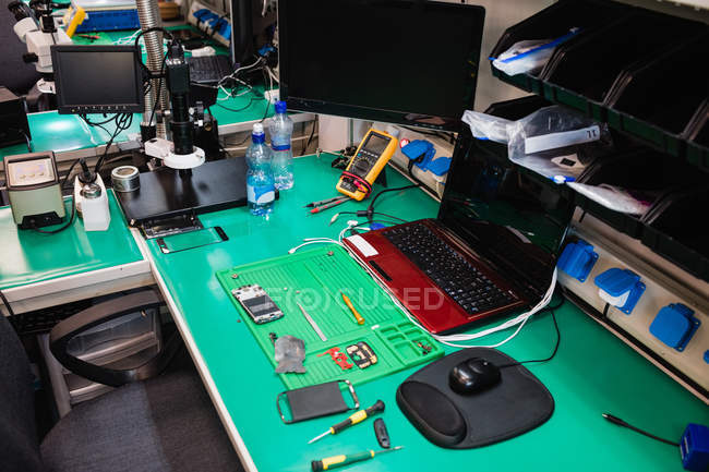 Desk with various equipment in an electronics repair centre — Stock Photo