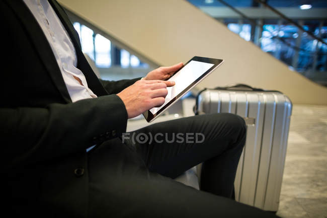Mid section of businessman using digital tablet at airport — Stock Photo