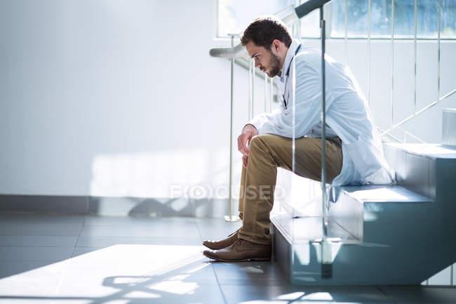 Médico triste sentado en la escalera en el hospital - foto de stock