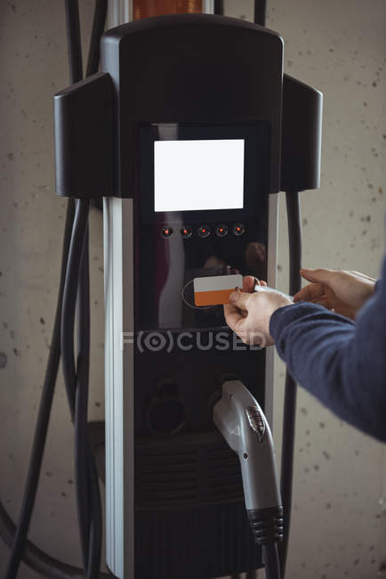 Man using plug-in electric machine at electric vehicle charging station — Stock Photo
