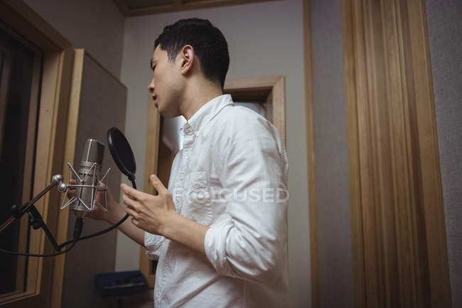 Man singing on microphone in recording studio — Stock Photo