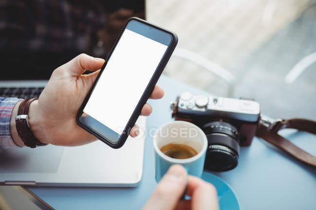 Hands of man holding smartphone while having coffee in cafeteria — Stock Photo