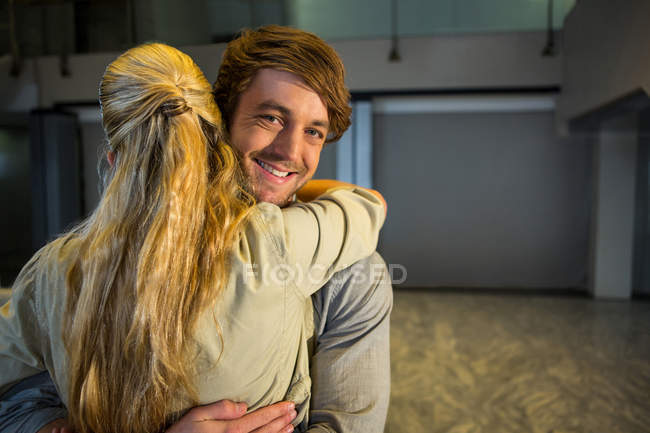 Cheerful couple embracing in airport terminal — Stock Photo