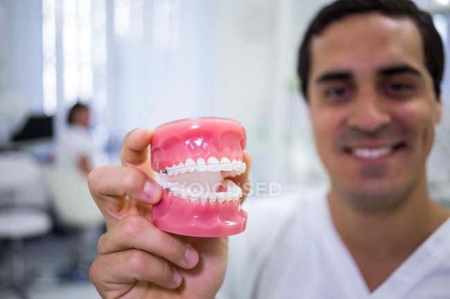 Mão de dentista segurando conjunto de dentaduras na clínica odontológica — Fotografia de Stock