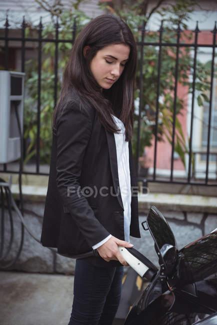 Beautiful woman charging electric car at vehicle charging station — Stock Photo