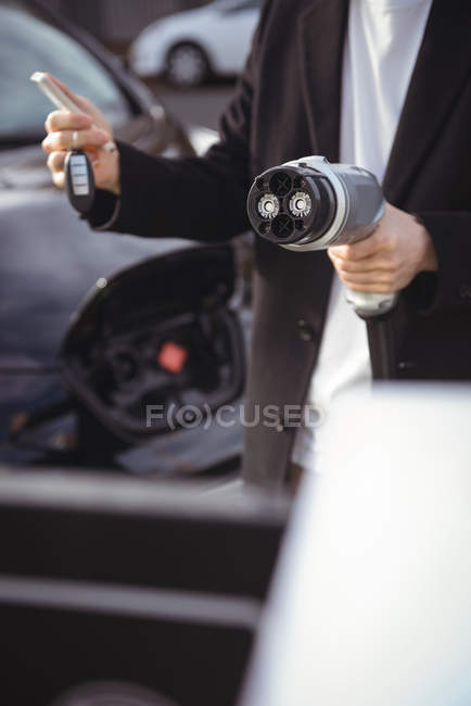 Mid section of man using mobile phone while holding car charger at electric vehicle charging station — Stock Photo