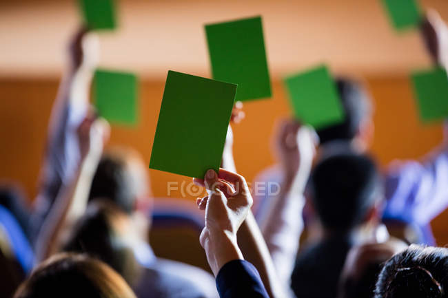 Rear view of business executives showing approval by raising hands at conference center — Stock Photo