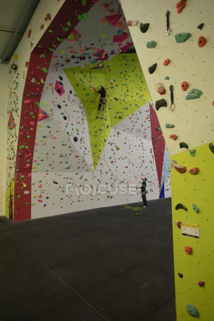 L'homme pratiquant escalade sur mur d'escalade artificiel au gymnase — Photo de stock