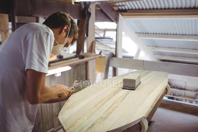 Мужчина делает доску для серфинга в интерьере мастерской — стоковое фото
