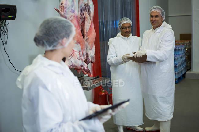 Boucherie-charcuterie interagissant avec technicien femmes à l'usine de viande — Photo de stock