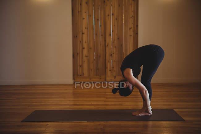 Frau beugt sich beim Yoga im Fitnessstudio — Stockfoto