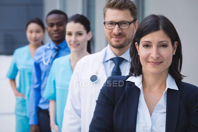 Retrato de sonriente médicos de pie en fila en las instalaciones del hospital - foto de stock