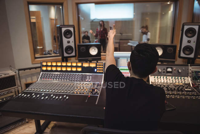 Audio engineer signaling to musicians while recording in studio — Stock Photo