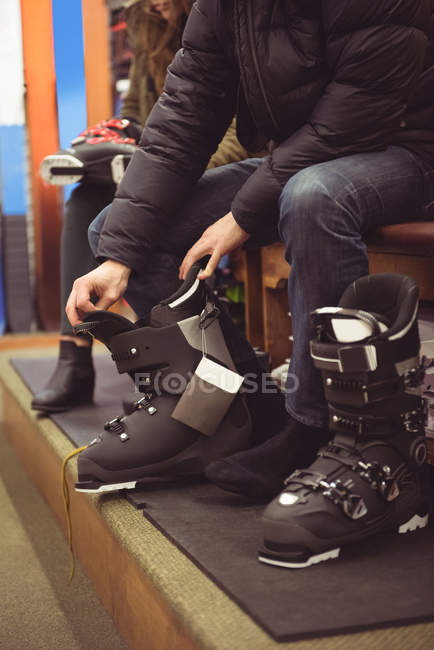 Close-up of man wearing a ski boots in a shop — Stock Photo