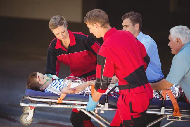 Paramédicos apressando um paciente em emergência na rua — Fotografia de Stock