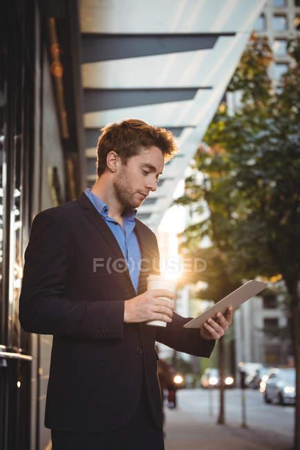 Uomo d'affari in possesso di tazza di caffè usa e getta e utilizzando tablet digitale mentre in piedi sulla strada — Foto stock