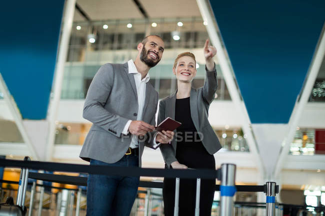 Businesswoman standing with her colleague and pointing at the distance at airport terminal — Stock Photo