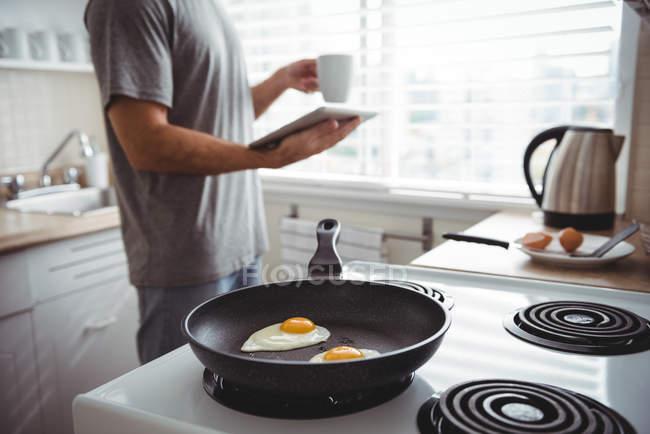 Homem usando tablet digital ao preparar ovos fritos na cozinha em casa — Fotografia de Stock