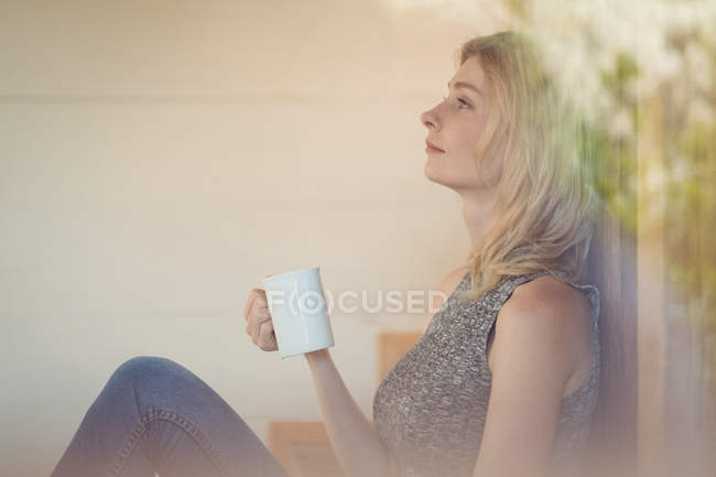 Thoughtful woman having coffee at home — Stock Photo