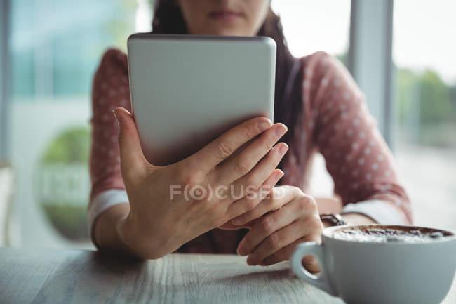 Sección media de la mujer que usa tableta digital mientras toma una taza de café en la cafetería - foto de stock
