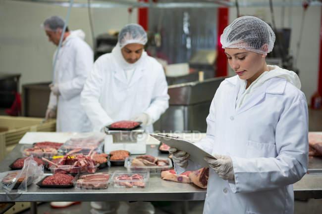 Жіночий м'ясника, ведення обліку у буфер обміну на заводі м'яса — стокове фото
