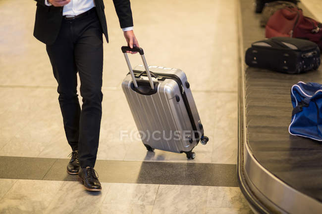 Businessman walking with luggage near baggage claim area at airport — Stock Photo