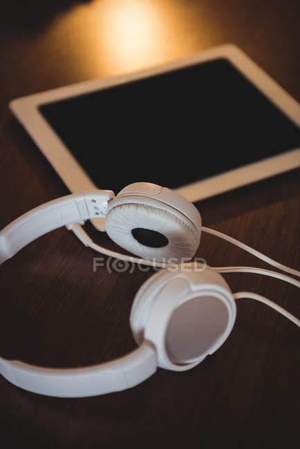 Close-up of headphones and digital tablet on wooden table at home — Stock Photo