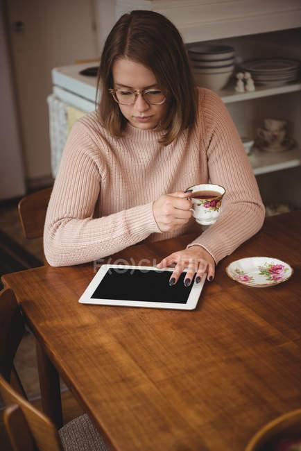 Mujer usando tableta digital mientras sostiene la taza de café en casa - foto de stock