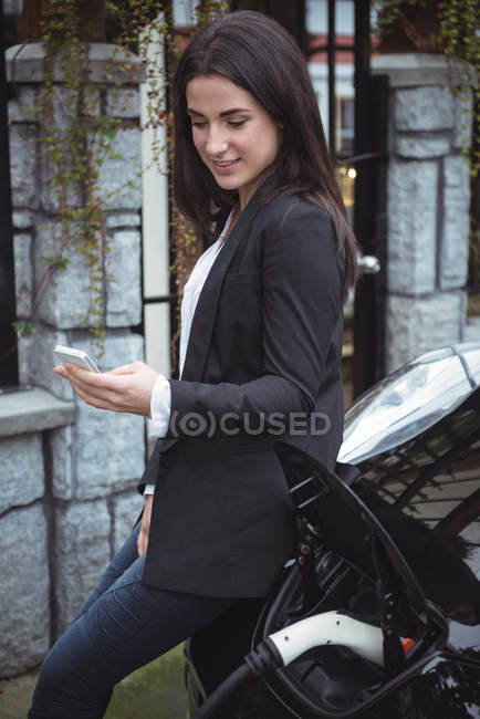 Beautiful woman using mobile phone while charging electric car at vehicle charging station — Stock Photo