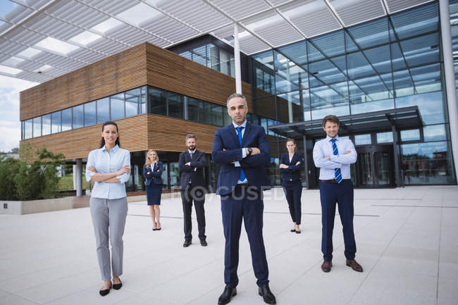 Group of confident businesspeople standing with arms crossed outside office building — Stock Photo