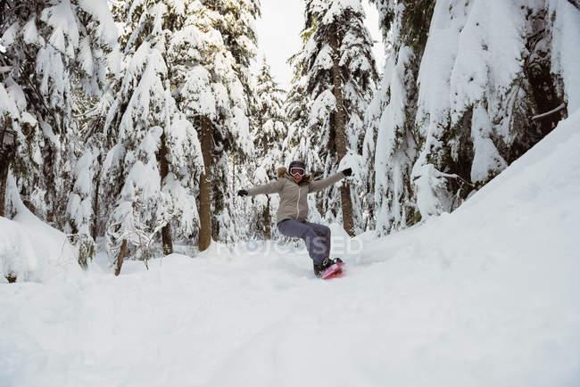 Woman snowboarding on snowy mountain slope — Stock Photo