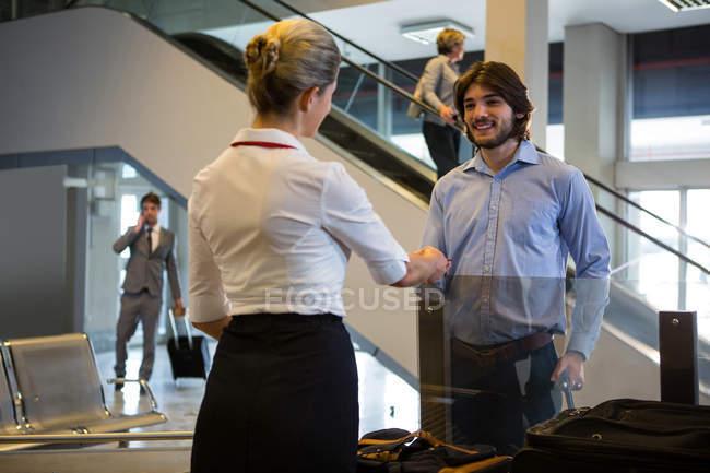Funcionários do sexo femininos, verificar o cartão de embarque de passageiros no balcão de check-in no aeroporto — Fotografia de Stock