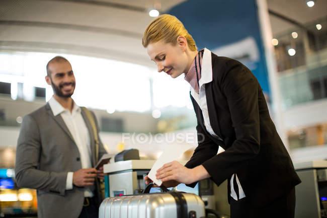 Línea aérea llegadas asistente pegarse etiquetas para el equipaje de un viajero en el aeropuerto - foto de stock
