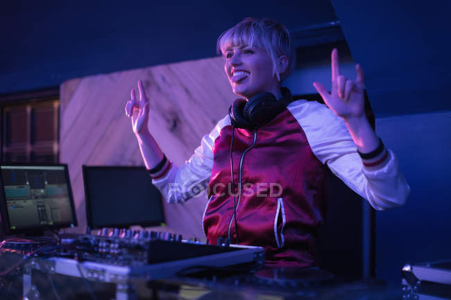 Pretty female dj making rock gesture while playing music in bar — Stock Photo