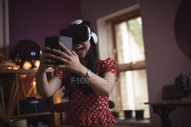 Mujer feliz usando auriculares de realidad virtual mientras sostiene un teléfono móvil en casa - foto de stock