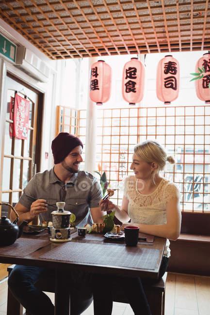 Пара, взаимодействующих друг с другом, имея суши в ресторане — стоковое фото