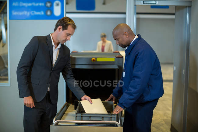 Airport security officer checking package of passenger in airport — Stock Photo