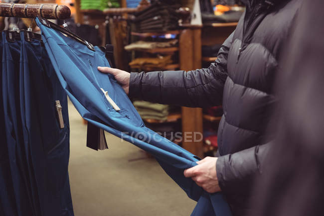 Закри людина виборі одягу в магазині одягу — стокове фото