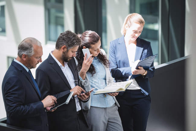 Uomini d'affari che utilizzano telefono cellulare e tablet digitale in ufficio — Foto stock