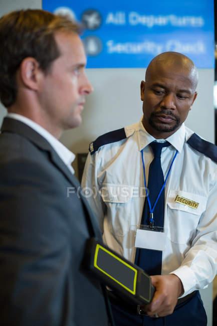 Сотрудник службы безопасности аэропорта, используя руку провел детектор металла для проверки регулярного пассажира пригородных поездов в аэропорту — стоковое фото