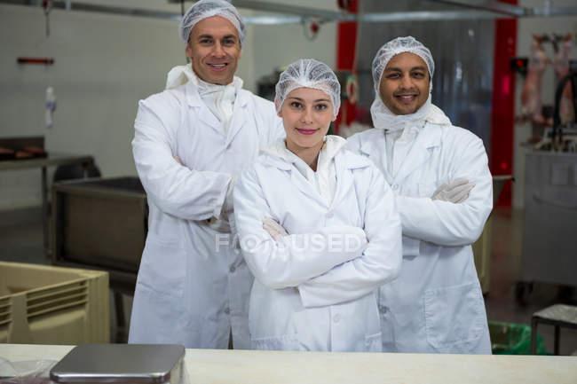 Equipe de açougueiros de pé com os braços cruzados na fábrica de carne — Fotografia de Stock