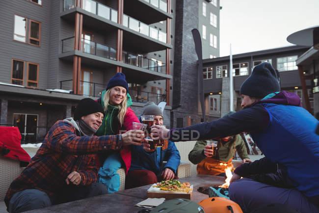 Heureux skieurs amis toasting verres de bière dans la station de ski — Photo de stock