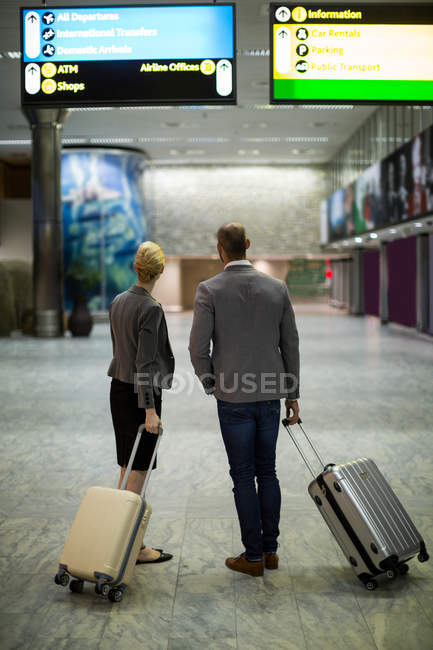Rear view of business people with luggage at airport terminal — Stock Photo