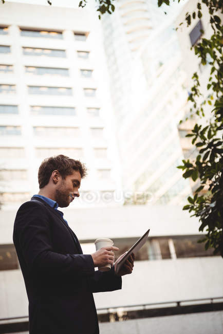 Businessman holding coffee cup and using digital tablet on street — Stock Photo