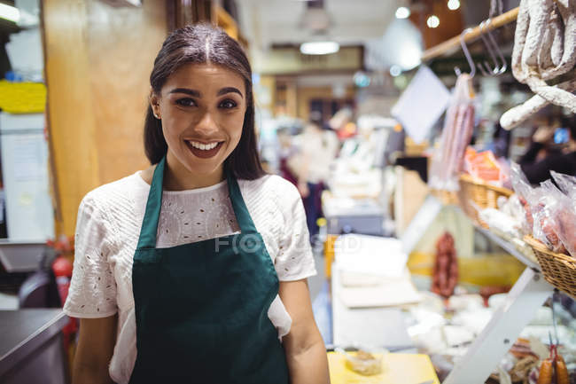 Portrait of female staff standing at meat counter in supermarket — Stock Photo