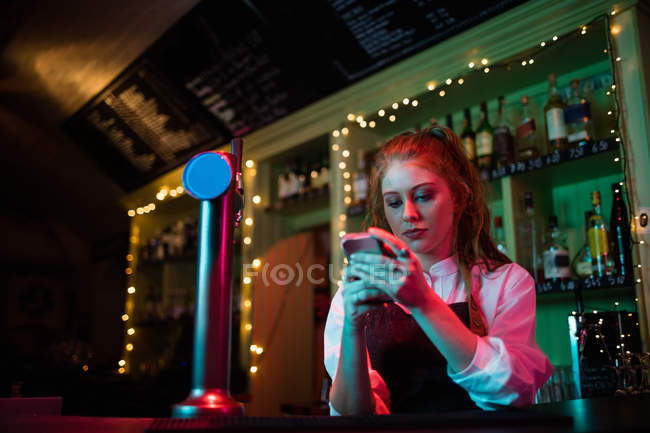Waitress using her mobile phone at counter in bar — Stock Photo