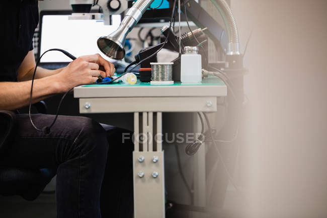 Man repairing an electronic device using soldering iron in service center — Stock Photo