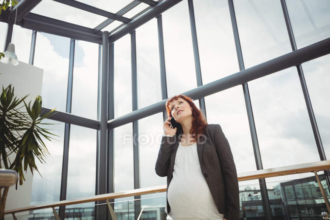 Pregnant businesswoman talking on mobile phone near corridor in office - foto de stock