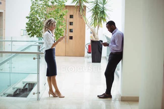 Руководители предприятий, использование мобильных телефонов в коридоре офиса — стоковое фото