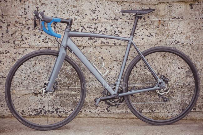 Bicicleta estacionada contra a parede grungy — Fotografia de Stock